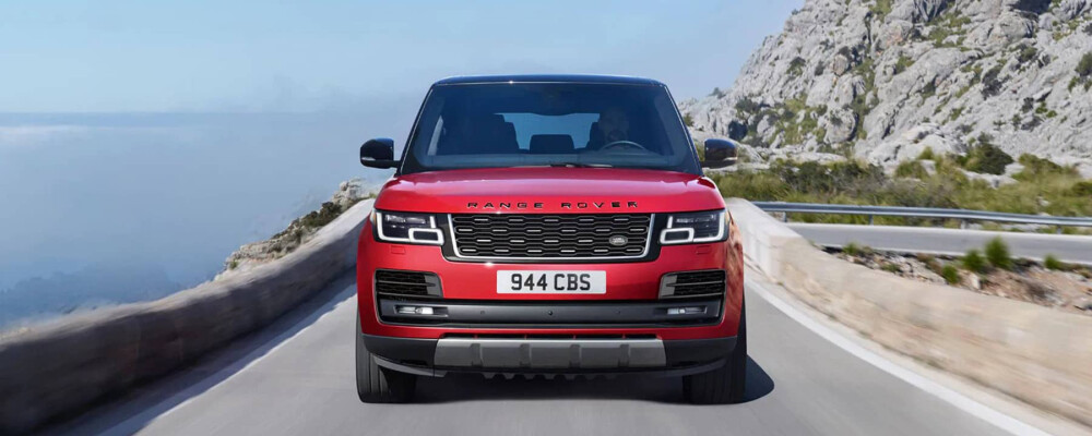 Red Range Rover driving on highway