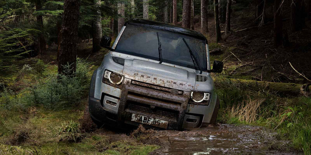 Defender driving through muddy water in forest