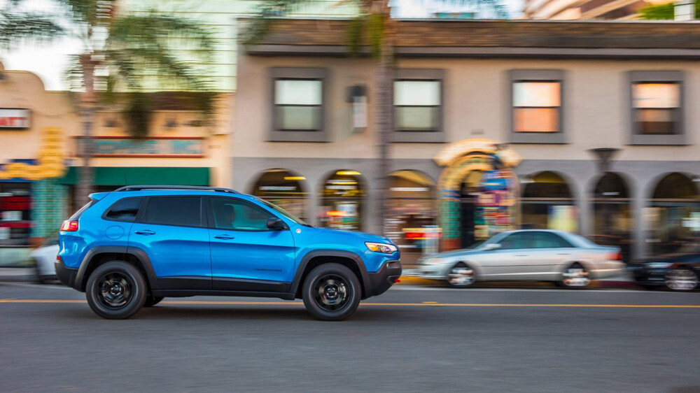 blue jeep cherokee driving through city