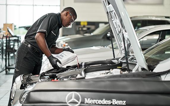 Mercedes-Benz technician servicing a vehicle with a Mercedes-Benz oil change