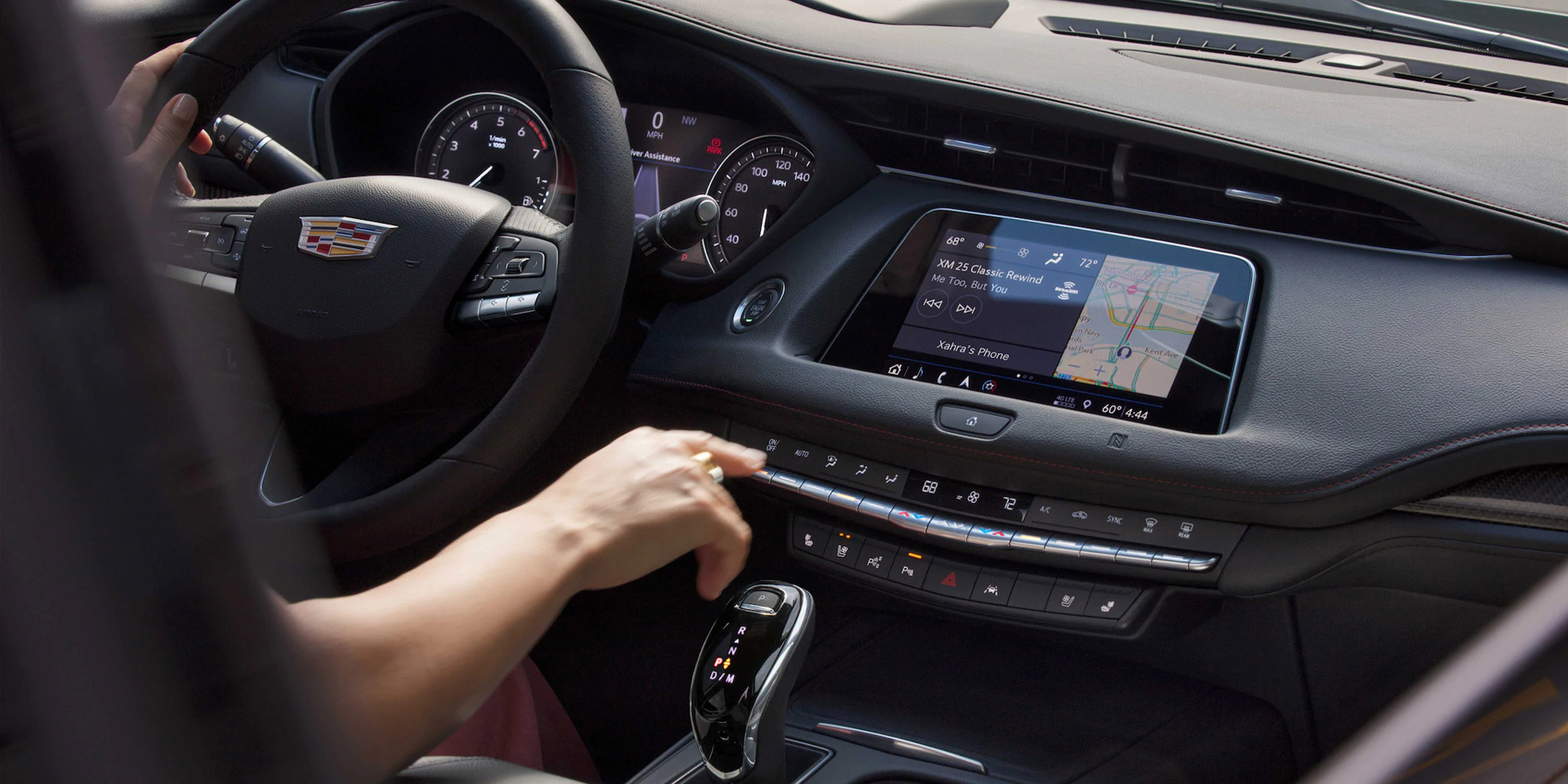 Woman driving a Cadillac XT4 is pushing buttons on the center console.